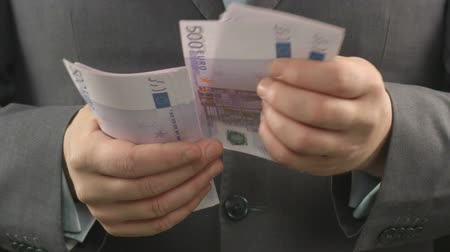 vesztegetés : Man in grey suit counting euros, close up of businessmans hands holding cash