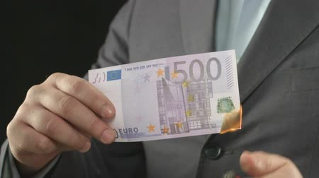 financiele crisis : Mannetje in kostuum die euro rekening, gelddevaluatie, inflatie en crisis, close-up branden