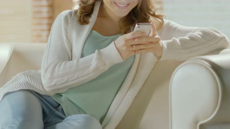 чат : Young attractive woman relaxing on couch and chatting with husband on smartphone