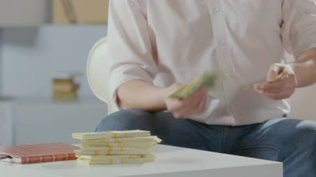 affluent : Rich man counting dollars in hands, putting them on table next to wads, wealth Stock Footage