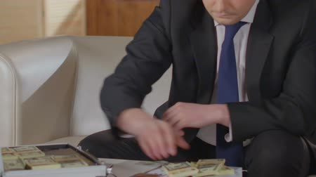 redemption : Businessman finishing call on cell phone, putting wads of dollars into suitcase Stock Footage