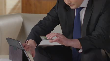 легкий : Man in business suit typing credit card number on tablet screen, paying bills
