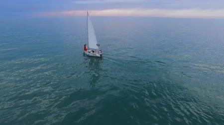 enjoyable : White sailing boat with couple at bow swimming down sea towards horizon, future Stock Footage