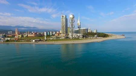 betűrendes : Batumi seafront park with Alphabetic Tower against cityscape, aerial zooming in Stock mozgókép