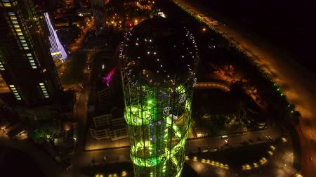 betűrendes : Aerial view of Alphabetic tower in Batumi, sparkling colorful lights at night Stock mozgókép