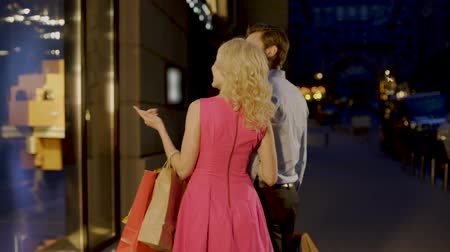 fashion outlet : Beautiful couple strolling through evening market street looking at shop windows