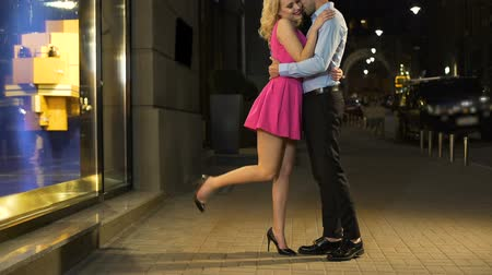 night life : Young and happy people lovely embracing, standing in brightly illuminated street Stock Footage