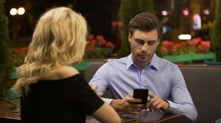 привлекать : Woman trying to attract attention of her boyfriend who actively working on phone Стоковые видеозаписи