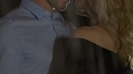 sensuous : Strong secure man hugging beautiful blond girl under rain, romantic evening date Stock Footage