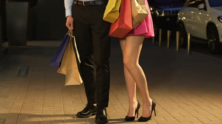 expenditure : Girl in short dress standing with guy in street, shopping day, only legs in shot