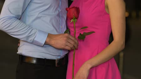 gentleness : Male giving rose to female, beginning of romantic relationship, tenderness, date