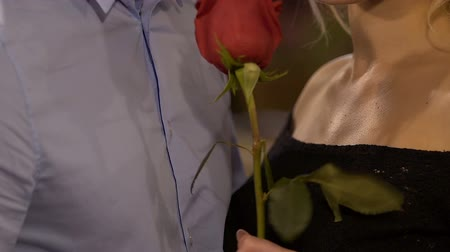 szentimentális : Male and female standing closely holding red rose, woman smelling it, tenderness