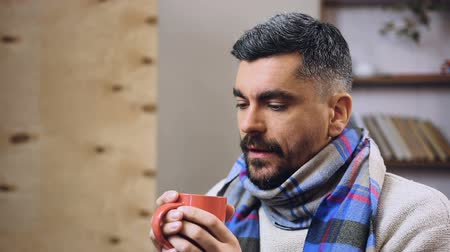 hangtompító : Feeble diseased male drinking hot tea with medicine to remove influenza symptoms Stock mozgókép