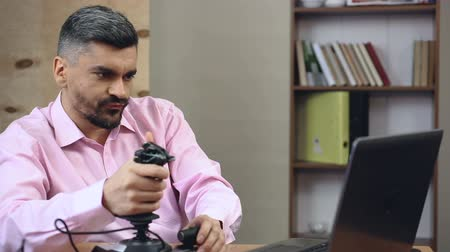 урод : Adult man wasting time at work, playing shooter video games with joystick Стоковые видеозаписи