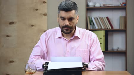 költő : Concentrated old-school author typing book on vintage typewriter in his office Stock mozgókép