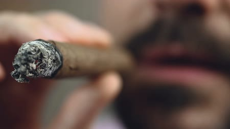 гордый : Closeup of burning Cuban cigar end, bearded man enjoying smoke, bad habit