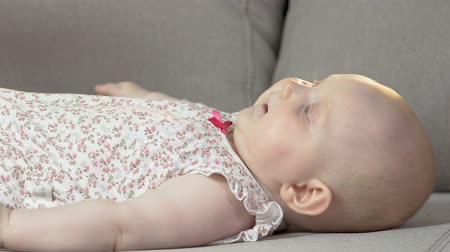 infant formula : Baby lying on back on couch kicking arms and legs, energetic child, infancy