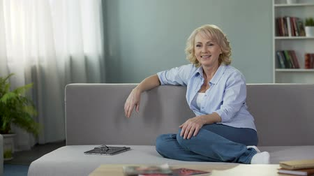 on camera : Gorgeous mature female sitting on couch and looking into camera, advertisement