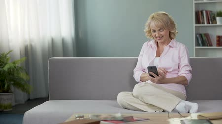 утилита : Blond senior woman paying utility bills online, using smartphone. Applications
