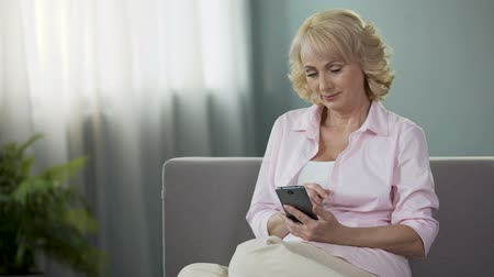 memories photos : Nice mature female sitting on sofa and viewing daughters photos on smartphone