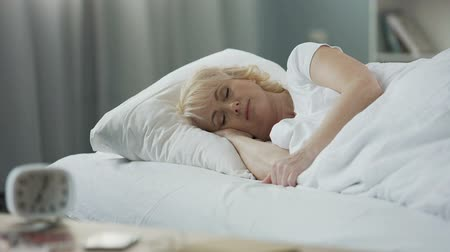 peaceful : Attractive mature female sleeping in her bed, rest at home, healthy lifestyle