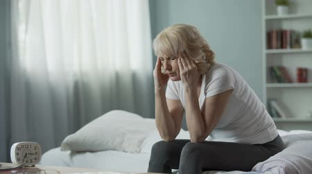 головная боль : Senior woman sitting on bed and suffering from terrible headache, health problem