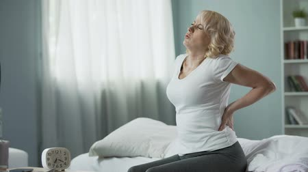 fájdalmas : Blond mature lady sitting on bed and touching her back, radiculitis and pain Stock mozgókép