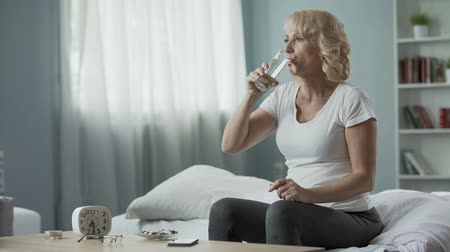 капсулы : Satisfied middle-aged female taking vitamins and drinking water, healthcare Стоковые видеозаписи