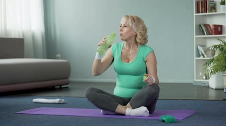 tartás : Athletic senior woman sitting on the floor and drinking water after workout Stock mozgókép