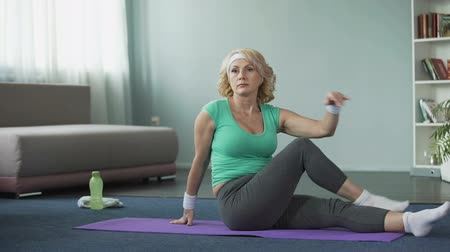 casa di riposo : Beautiful mature female practicing Twisting Sage pose at home, yoga time, sport Filmati Stock