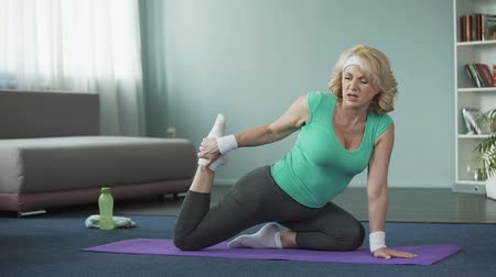 çabaları : Tired mature woman doing yoga exercises, stretching legs. Healthy lifestyle