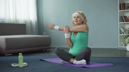 çabaları : Healthy mature female doing fitness exercises on yoga mat, training at home