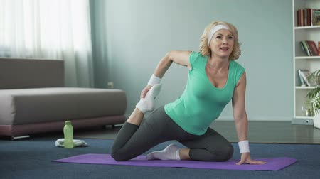 çabaları : Blond middle-aged female doing stretching exercises on yoga mat at home, sport