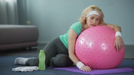 çabaları : Exhausted mature female lying on fitness ball, relaxing after active workout