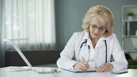 patienten : Lady doctor filling in health insurance form before proceeding to treat patient Videos