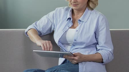 e book : Senior woman sitting on couch and scrolling screen of tablet, reading e-book