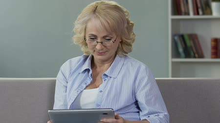 holding newspaper : Senior female putting on glasses and looking at tablet, reading online newspaper Stock Footage