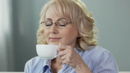 восхитительный : Elderly lady sitting on sofa, taking cup of tea enjoying smell, relax at home