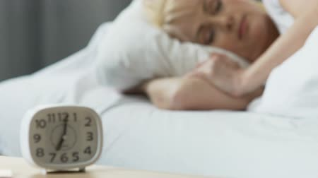 часов : Alarm clock standing on nightstand, woman sleeping in bed, comfort at home