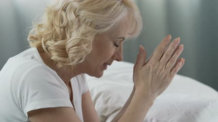believer : Woman of senior age praying at her bed, eyes closed, smiling, gratitude to God