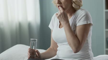 pensão : Retired woman taking pill, drinking it up with water, health troubles medication