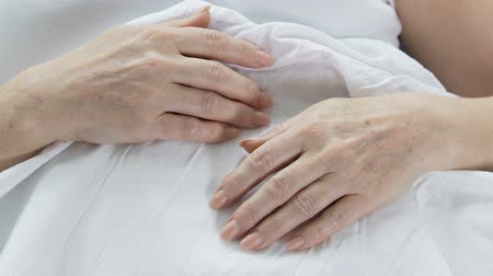 move well : Hands of elderly woman lying in bed, wrinkled skin, aging person, experience Stock Footage