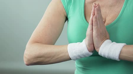 another : Aged female putting palms one against another in yoga lotus position, hobby