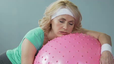 çabaları : Sleepy tired middle-aged woman lying on fitness ball after active workout Stok Video