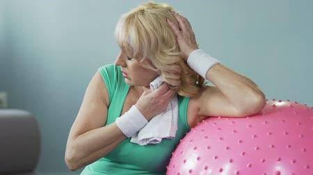 feszült : Elderly female leaning on fitness ball fanning herself with towel, exhaustion Stock mozgókép
