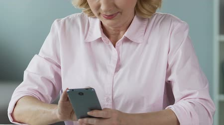 görgetés : Female in her 50s scrolling news in social networks on smartphone, close-up
