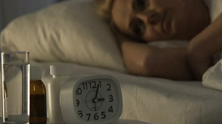febre : Ill female pensioner lying in bed and suffering from insomnia, health problems Stock Footage