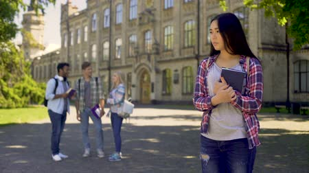 outsider : Lonely biracial girl standing alone, upset about mockery and jokes of classmates Stock Footage