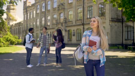 amigos : Joyful blonde girl standing away from her classmates, waiting for boyfriend Vídeos