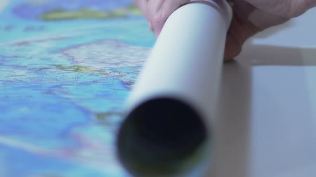 óceánok : Hands rolling up world map poster and taking it away from the table, slow motion